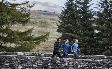Three runners on a bridge in winter